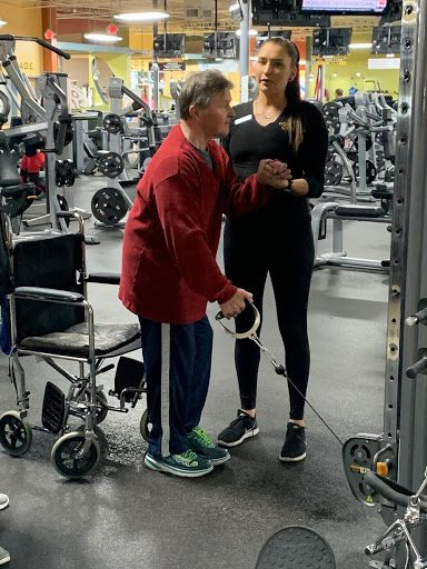 Paul working with a trainer at gold's gym